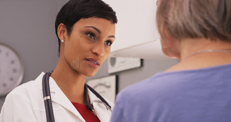 Young intelligent female doctor talking to elderly patient royalty free stock photography