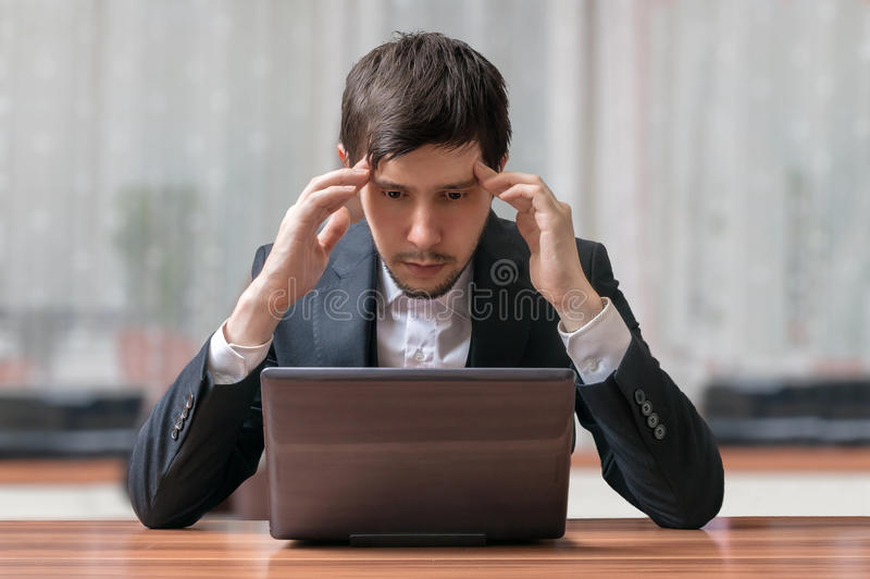 Young intend and thinking businessman working with laptop royalty free stock images