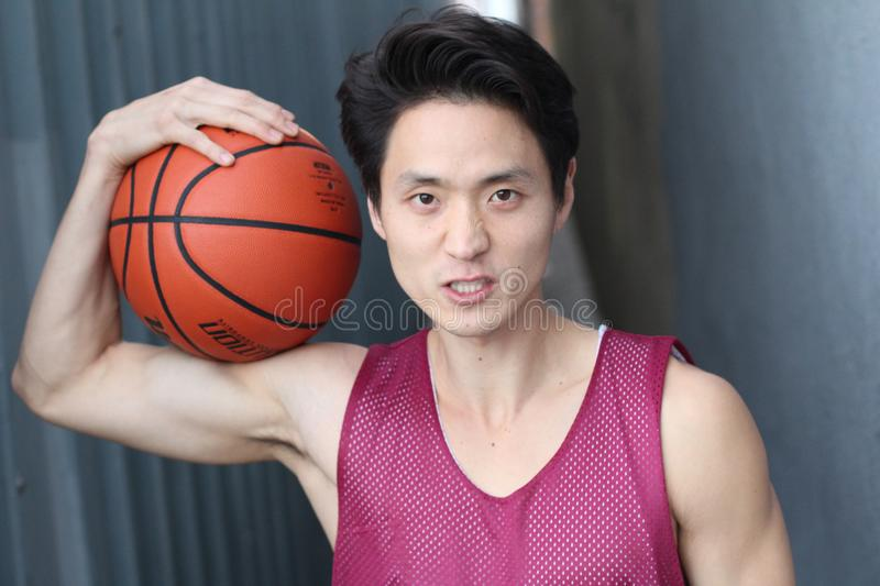 Young intense Asian male holding basketball royalty free stock photography