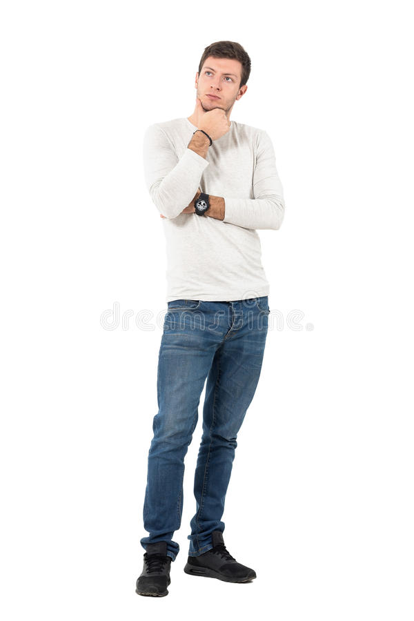 Young interested casual man at attention looking away. Full body length portrait isolated over white studio background stock photography