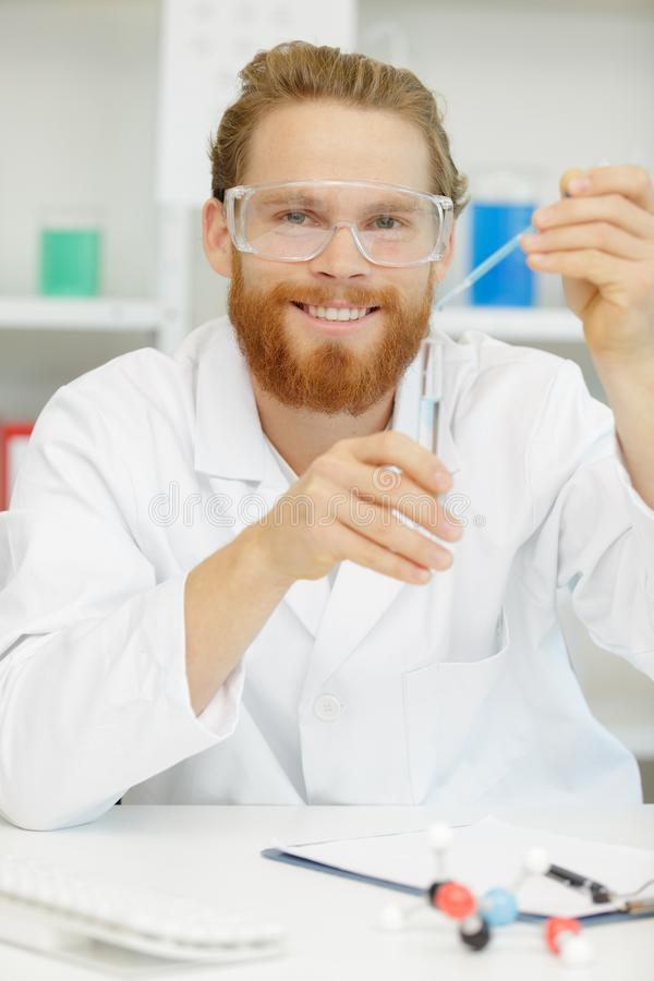 Young interested scientist keeping and overlooking test tube royalty free stock image