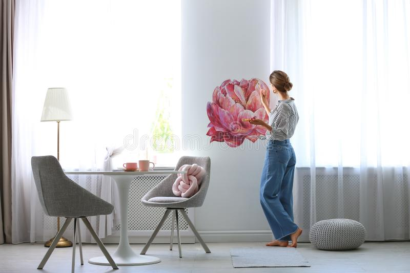 Young  designer painting flower on wall in modern room stock photo