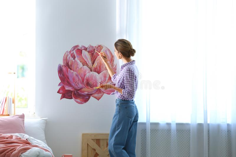 Young interior designer  flower on wall in modern room royalty free stock image
