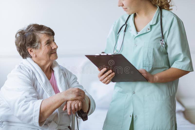 Young intern doctor with pad and stethoscope and elderly grandmother with cane stock images