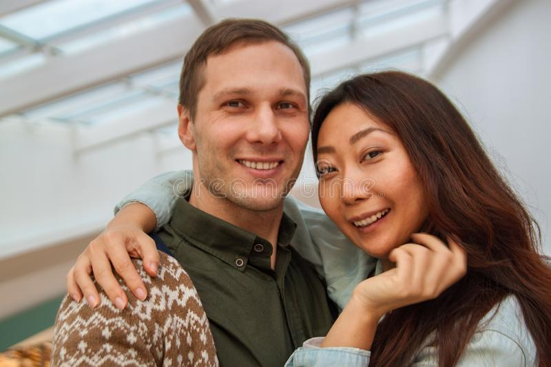 Young international couple taking selfie in the mall. stock photos