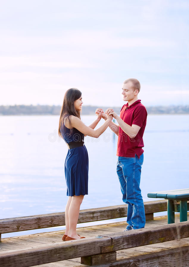 Young interracial couple holding hands standing on dock over lake royalty free stock photography
