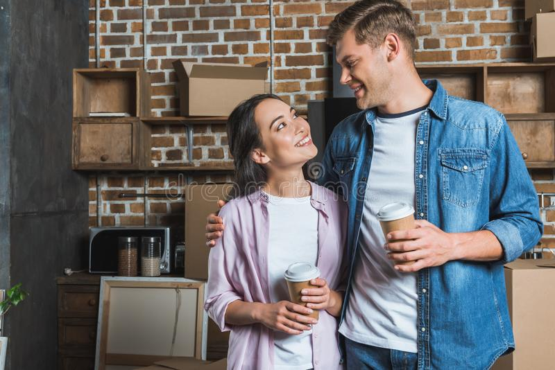 Young interracial couple with paper cups of coffee standing on kitchen while moving into new home and looking. At each other stock images