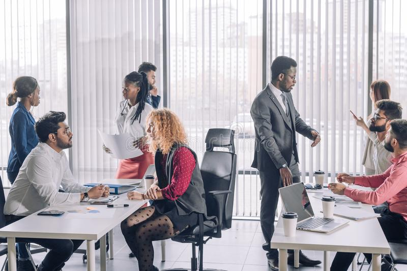 Multiracial business coworkers talking, interacting on workplaces. Young interracial coworkers sitting at open space office together, working on laptops stock photo