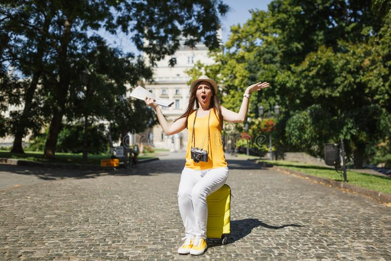 Young irritated angry traveler tourist woman in yellow clothes sitting on suitcase hold city map spreading hands outdoor stock image