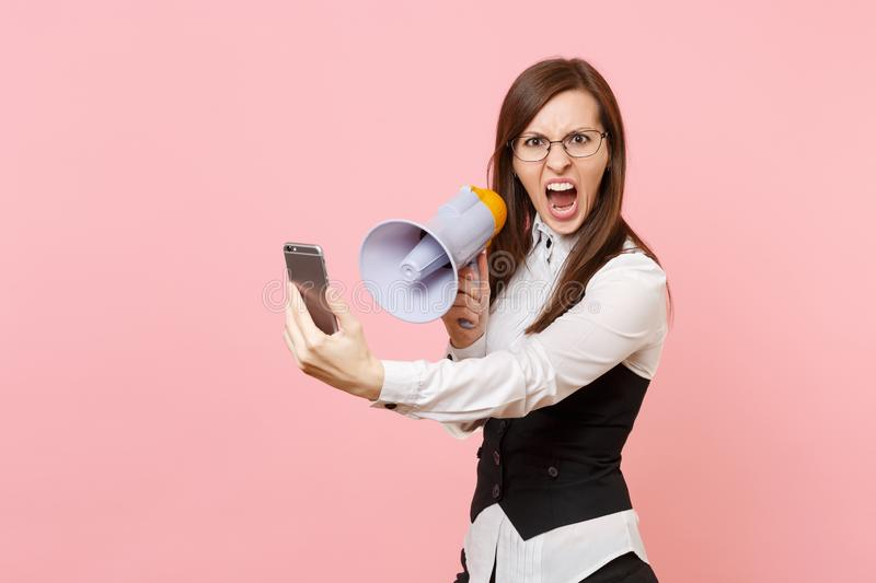 Young irritated dissatisfied business woman in glasses screaming holding megaphone and mobile phone on pink stock image