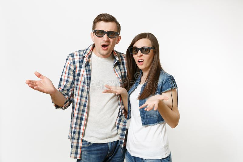 Young irritated dissatisfied couple, woman and man in 3d glasses and casual clothes watching movie film on date and royalty free stock photography