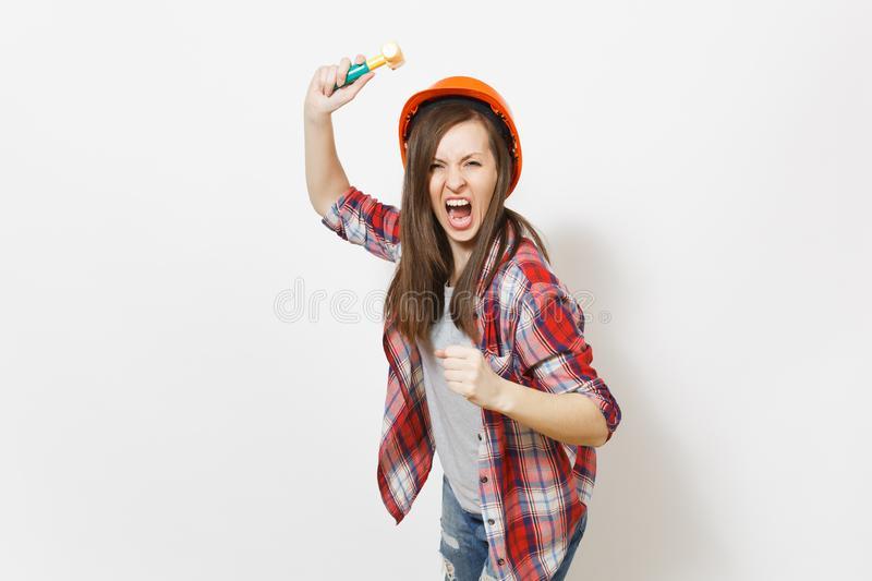 Young irritated dissatisfied woman in protective construction helmet swinging toy hammer and screaming isolated on white stock images