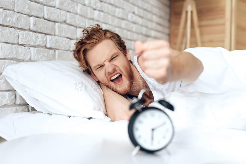 Young, irritated man reaches out to turn off stock photo