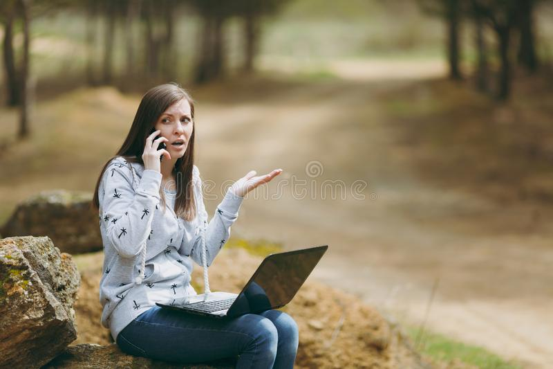 Young irritated smart business woman or student in casual clothes sitting on stone using mobile phone and laptop in city stock image