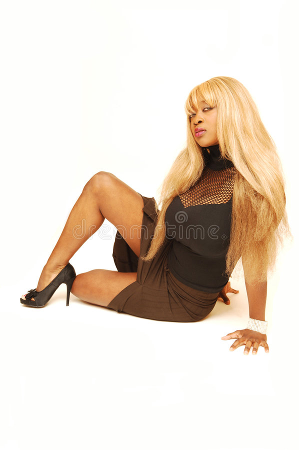 Young Jamaican girl. An busty young Jamaican girl in a black top and brown skirt with long blond hair sitting on the floor in a studio for white background royalty free stock photo