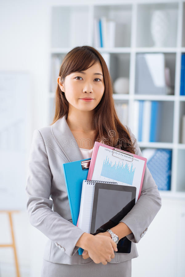 Young Japanese business woman. Portrait of young Japanese business woman holding documents and digital tablet royalty free stock photo