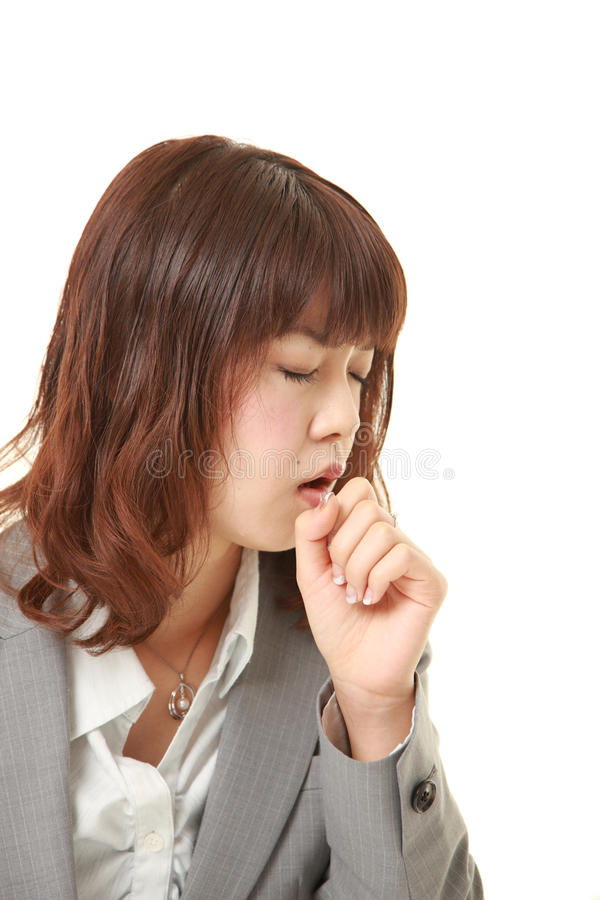 Young Japanese businesswoman coughing. Studio shot of young Japanese businesswoman on white background royalty free stock photo