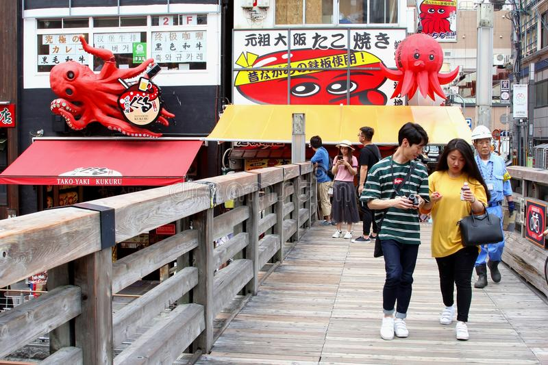 Young Japanese couples wooden bridge, Dotonbori, Osaka. Young Japanese couples are walking on wooden bridge over the Dotonbori river along restaurants with three stock photography