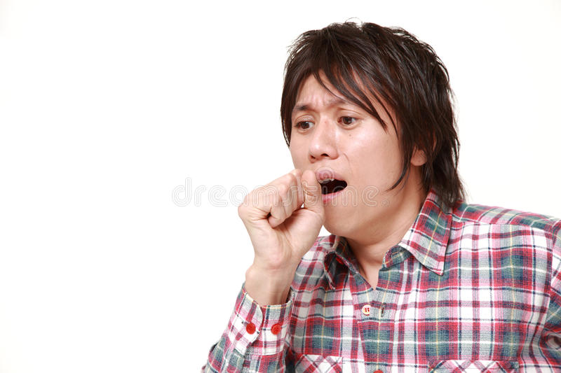 Young Japanese man coughing . Studio shot of young Japanese man on white background stock photography