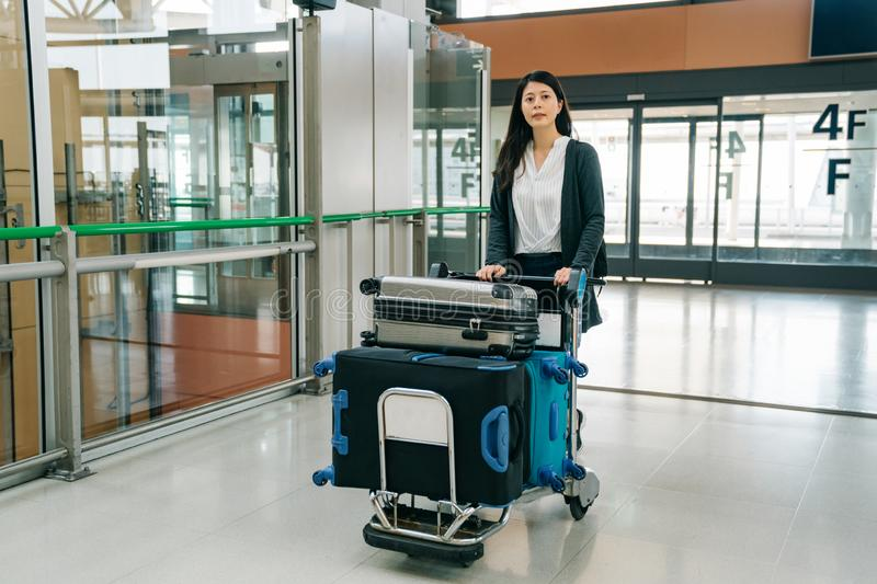 Young japanese office lady enter to the hall. Asian manager walking in kansai international airport pushing luggage cart. young japanese office lady enter the royalty free stock photos