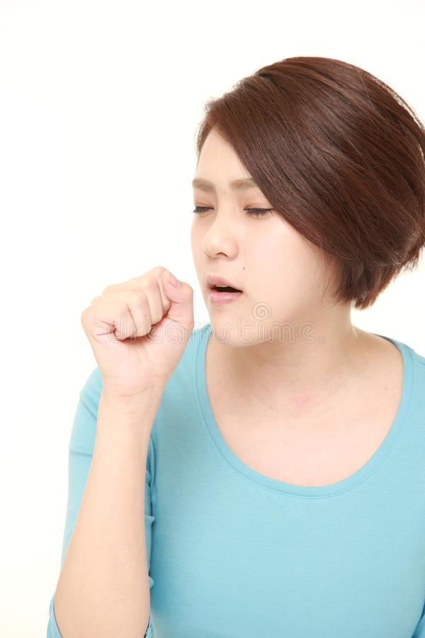 Young Japanese woman coughing. Studio shot of young Asian woman wearing blue shirt on white background royalty free stock photos