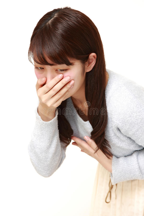 Young Japanese woman feels like vomiting. Studio shot of young Japanese woman on white background stock photo