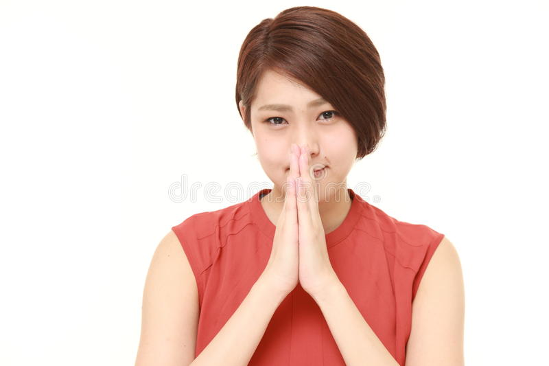 Young Japanese woman folding her hands in prayer. Studio shot of young Japanese woman on white background stock image