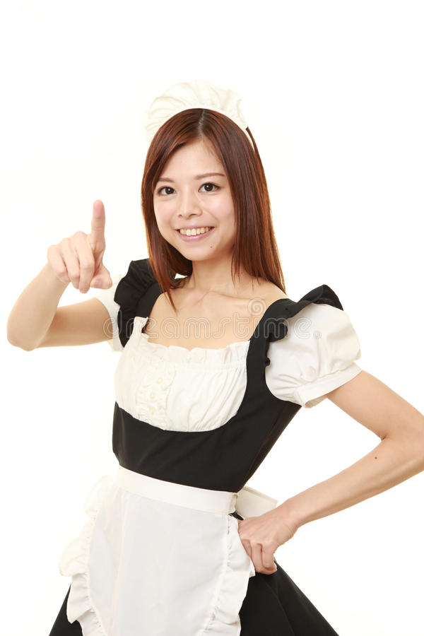 Young Japanese woman wearing french maid costume presenting and showing something royalty free stock image