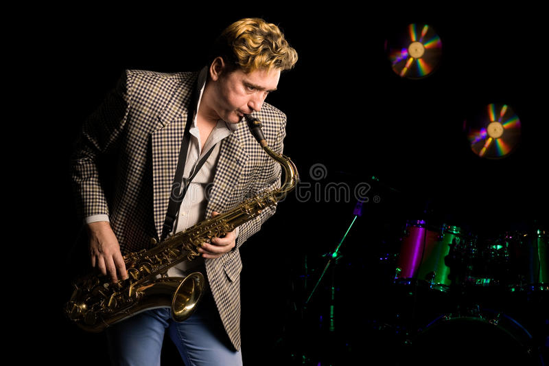 Young jazz musician with saxophone. In the background, music drums kit stock photography