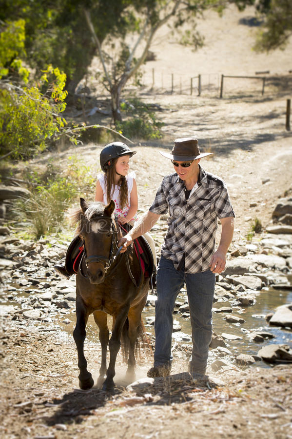 Young jockey kid riding pony outdoors happy with father role as horse instructor in cowboy look. Cute young girl jockey having fun and riding pony outdoors happy royalty free stock images