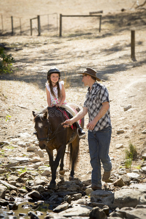 Young jockey kid riding pony outdoors happy with father role as horse instructor in cowboy look. Cute young girl jockey having fun and riding pony outdoors happy royalty free stock image