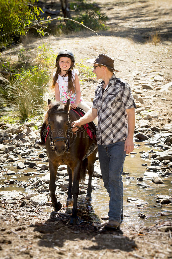 Young jockey kid riding pony outdoors happy with father role as horse instructor in cowboy look. Cute young girl jockey having fun and riding pony outdoors happy stock photos