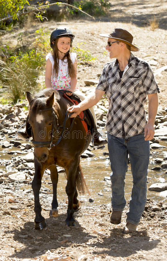 Young jockey kid riding pony outdoors happy with father role as horse instructor in cowboy look. Cute young girl jockey having fun and riding pony outdoors happy royalty free stock photography