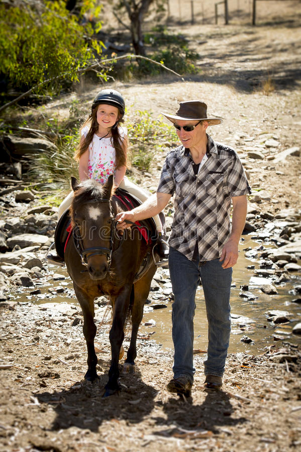 Young jockey kid riding pony outdoors happy with father role as horse instructor in cowboy look. Cute young girl jockey having fun and riding pony outdoors happy stock photo