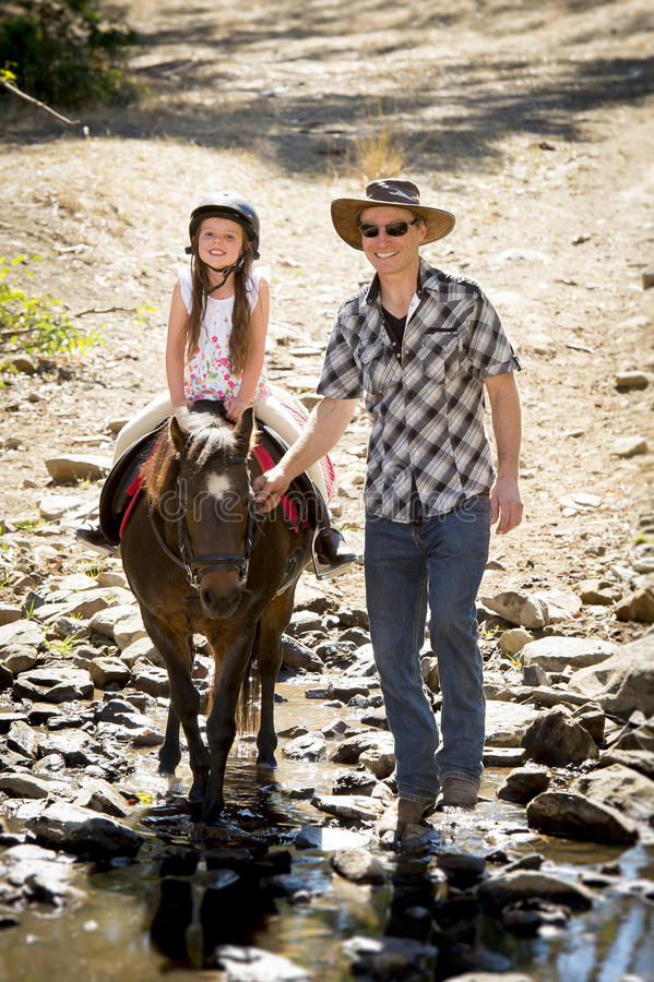 Young jockey kid riding pony outdoors happy with father role as horse instructor in cowboy look. Cute young girl jockey having fun and riding pony outdoors happy royalty free stock photo