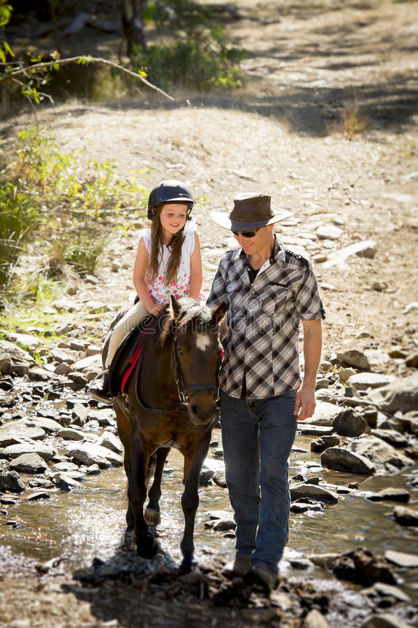 Young jockey kid riding pony outdoors happy with father role as horse instructor in cowboy look. Cute young girl jockey having fun and riding pony outdoors happy stock image