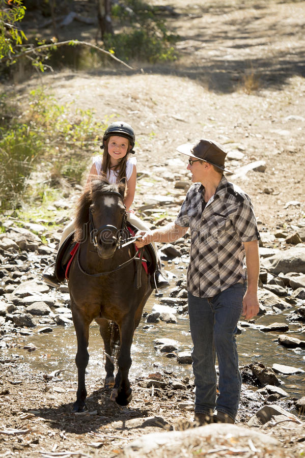Young jockey kid riding pony outdoors happy with father role as horse instructor in cowboy look. Cute young girl jockey having fun and riding pony outdoors happy stock images