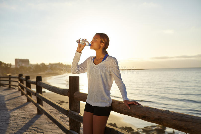 Young jogger drinking an energy drink stock photo