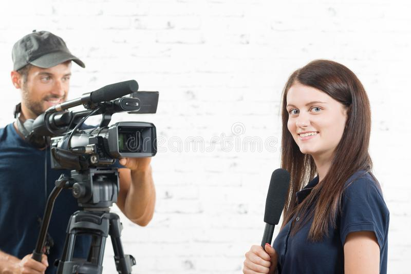 A young journalist and a cameraman. A young journalist with a microphone and a cameraman stock image