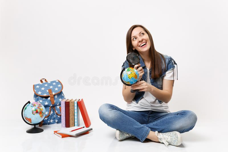Young joyful beautiful woman student holding world globe and magnifying glass sitting near backpack, school books royalty free stock images