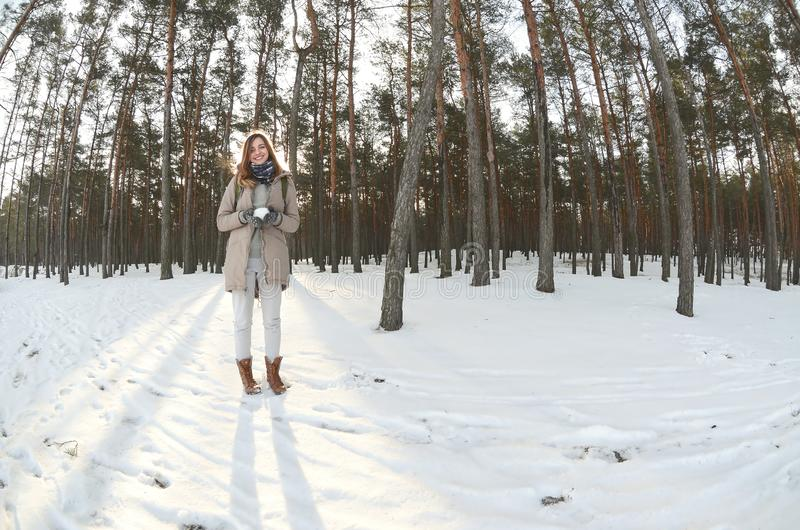 A young and joyful Caucasian girl in a brown coat holds a snowball in a snow-covered forest in winter. Fisheye Photo.  stock images