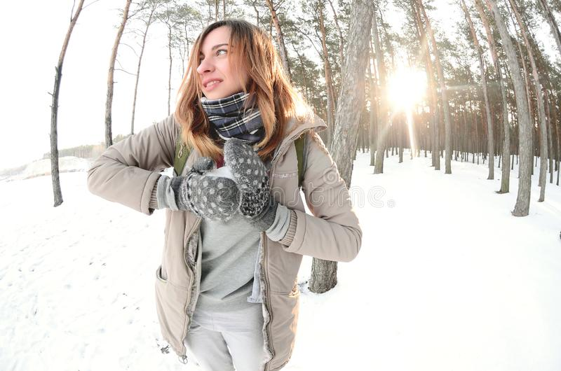 A young and joyful Caucasian girl in a brown coat sculpts a snowball in a snow-covered forest in winter. Games with snow in the stock photo