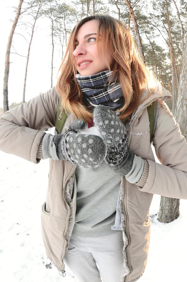 A young and joyful Caucasian girl in a brown coat sculpts a snowball in a snow-covered forest in winter. Games with snow in the royalty free stock images