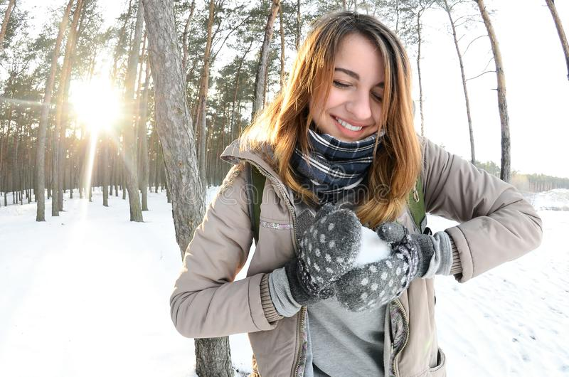 A young and joyful Caucasian girl in a brown coat sculpts a snowball in a snow-covered forest in winter stock image