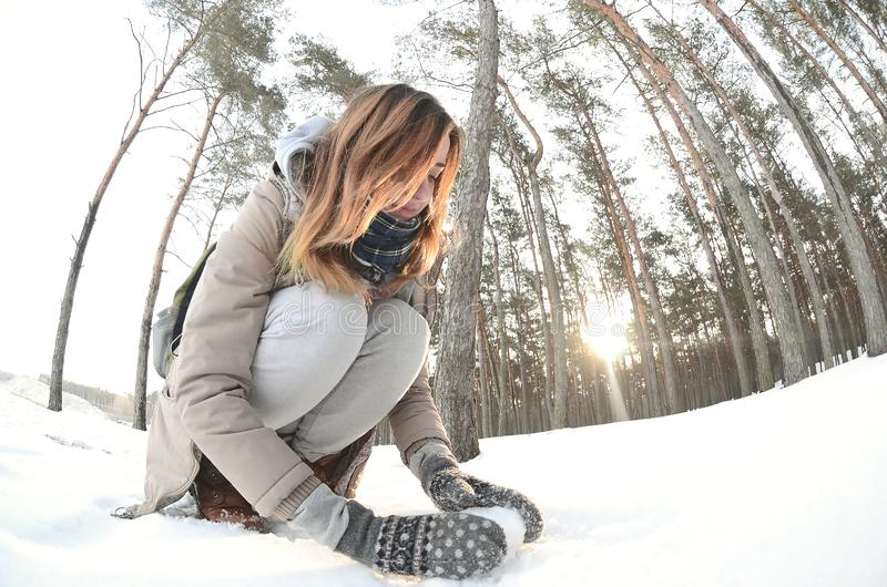 A young and joyful Caucasian girl in a brown coat sculpts a snowball in a snow-covered forest in winter. Games with snow in the royalty free stock photography