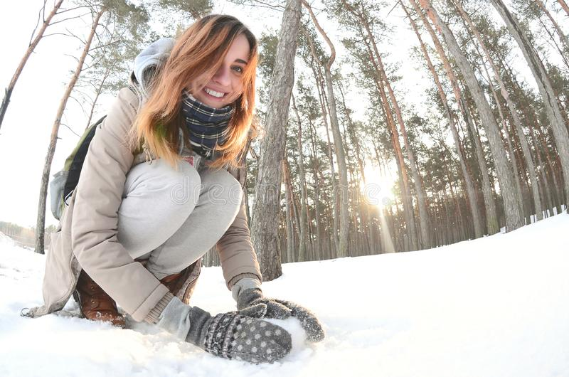 A young and joyful Caucasian girl in a brown coat sculpts a snowball in a snow-covered forest in winter. Games with snow in the stock photos
