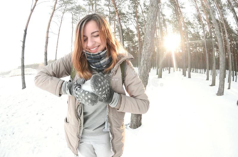 A young and joyful Caucasian girl in a brown coat sculpts a snowball in a snow-covered forest in winter. Games with snow in the stock images
