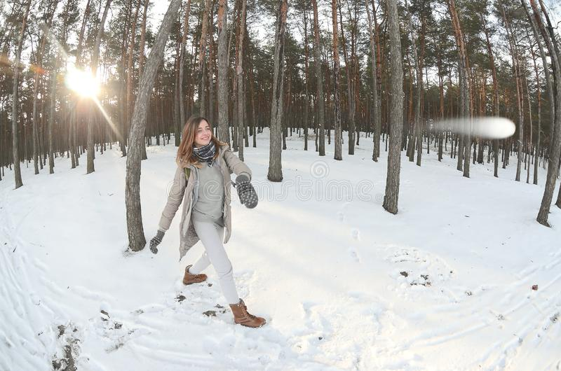 A young and joyful Caucasian girl in a brown coat is throwing a snowball in a snow-covered forest in winter. Games with snow in stock photography