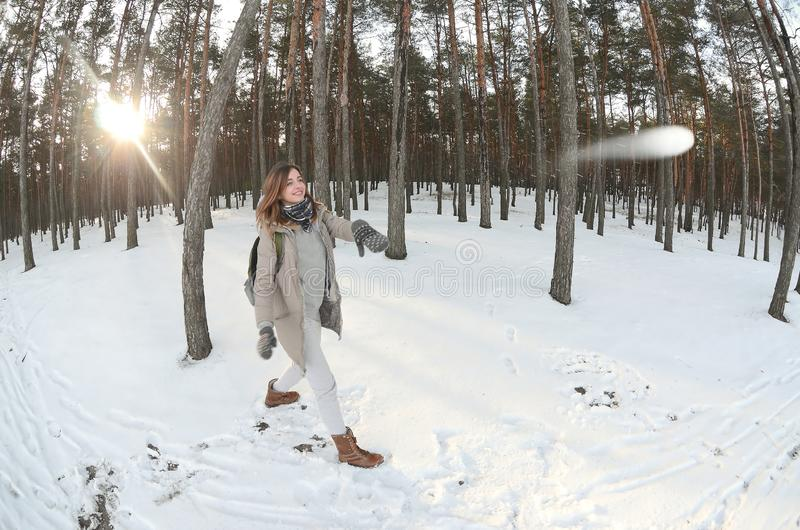 A young and joyful Caucasian girl in a brown coat is throwing a snowball in a snow-covered forest in winter. Games with snow in stock photo