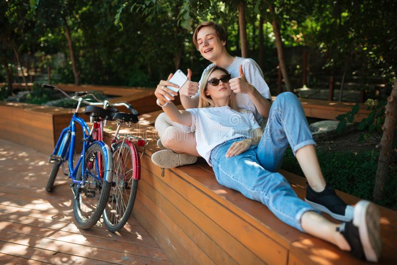 Young joyful couple spending time in park with bicycles nearby. Smiling boy sitting on bench in park with pretty girl stock image